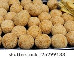 Sesame balls can be found in many Chinese bakeries. Chinese believe if you eat sesame balls, your fortunes will expand like the dough expands when it fries. - stock photo