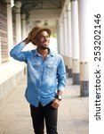 Small photo of Portrait of a happy young african american man walking with hat