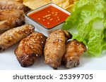 Grilled chicken wings with hot pepper sauce and salad - stock photo