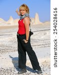 Athletic blonde girl locking in camera is pointing the hand in the direction and invites in a travel. Sahara desert. Travel concept - stock photo