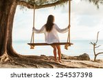 Girl Sitting On The Swing Near...