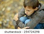 Little Sad Boy In Autumn Park