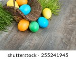 Colorful Easter eggs in a basket and green grass on a wooden table with copy space for text greetings