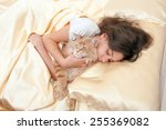 Stock photo girl sleeping in bed with her cat 255369082