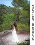 Small photo of beautiful girl wearing white flowy dress in forest. Back view