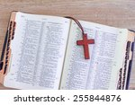 Small photo of Old open Bible ( American Standard version ) with cross over soft wood background