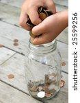 Child Places Coins Into A Mason ...