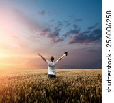 Small photo of man holding up Bible in a wheat field