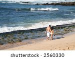 A couple holding hands walking on the beach - stock photo