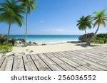 tropical beach and wooden deck  | Shutterstock . vector #256036552