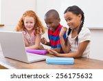 cute pupils using computer at... | Shutterstock . vector #256175632
