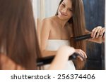 Woman Straightening Hair With...
