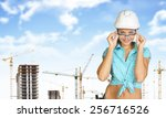 woman in hard hat adjusting... | Shutterstock . vector #256716526
