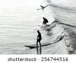 Three Silhouettes Of Surfers I...