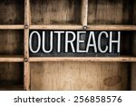 "Small photo of The word ""OUTREACH"" written in vintage metal letterpress type in a wooden drawer with dividers."
