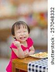 little asian girl eating puff... | Shutterstock . vector #257048332