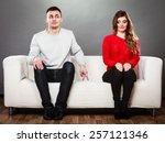 Small photo of Shy woman and man. Guy sitting near attractive young woman on sofa and making hand gesture walking with finger to girl