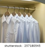 row of white shirts hanging on... | Shutterstock . vector #257180545
