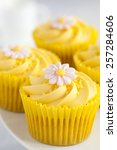 Small photo of Close up of Lemon cupcakes with butter cream swirl and fondant flower decorations