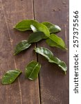 Small photo of Kafir lime leaves on a rustic wooden surface, ready to flavor food.