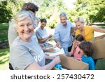 Small photo of Happy volunteer family separating donations stuffs on a sunny day