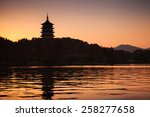 Black silhouette of traditional Chinese pagoda on orange evening sky background. Coast of West Lake. Famous park in Hangzhou city center, China