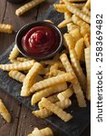 Small photo of Unhealthy Baked Crinkle French Fries with Ketchup