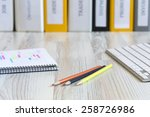 Stock photo side view on the working place of designer light wooden desk with color pencils notepad with 258726986