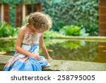 Little Girl Sitting By The Pond ...