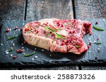 Beef with rosemary and pepper on black rock - stock photo