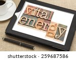 Small photo of vital energy typography - text in letterpress wood type blocks on a digital tablet with cup of coffee