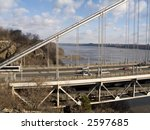 A close-up view of The George washington Bridge with the Palisades and Hudson River in the background. - stock photo