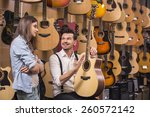 man is showing to girl guitar... | Shutterstock . vector #260572142
