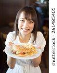 young woman eating hamburger at ... | Shutterstock . vector #261485405
