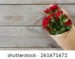 Stock photo red roses wrapped in paper on wooden table background 261671672