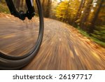Bicycle riding on country road. Autumn scene, low angle, motion blur. - stock photo