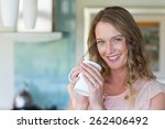 pretty blonde holding a mug at... | Shutterstock . vector #262406492