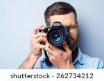 Focusing at you. Handsome young man photographing you while standing against grey background - stock photo