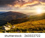 view on high mountains from hillside covered with grass with few stones near the path in sunset light - stock photo