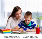 young mother sitting at a table ... | Shutterstock . vector #263418026