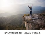 young woman standing on cliff... | Shutterstock . vector #263744516
