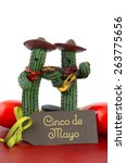 Small photo of Happy Cinco de Mayo concept with fun Mariachi Band Cactus players and greeting card on red wood table.