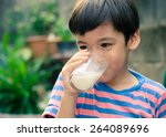 little boy drinking milk in the ... | Shutterstock . vector #264089696