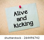 Small photo of Alive and kicking Message. Recycled paper note pinned on cork board. Concept Image