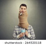 Stock photo sad man with long neck coiled scarf over dark background 264520118