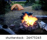 Campfire with tent in background for camping scene - stock photo