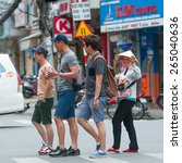 Small photo of HO CHI MINH, VIETNAM - JULY 6, 2014: Unidentified Asian tourists cross the road followed by a street pedlar woman. Street pedlars in Pham Ngu Lao usually sell small souvenirs and trifles.