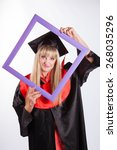 Small photo of Educational theme: graduating student girl in an academic gown holds the frame. Isolated over white background.