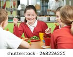 Stock photo group of pupils sitting at table in school cafeteria eating lunch 268226225