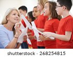 Small photo of Children In Singing Group Being Encouraged By Teacher